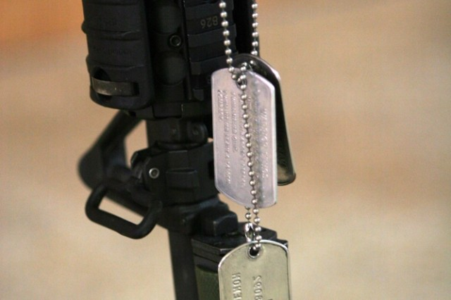 Dog tags with the name of Army Pfc. Aaron Ward hang on a memorial in honor of the Soldier who was killed, May 6, while on a combat patrol in western Anbar province, Iraq. A memorial service for the fallen Soldier was held at the chapel on Al Asad Air Base, Iraq, Friday. Pfc. Ward, 19, was a military policeman with 170th Military Police Company, 504th Military Police Battalion, which is attached to Regimental Combat Team 5.