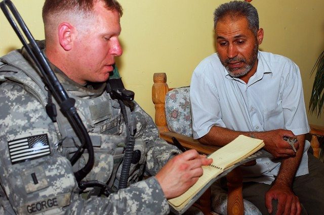 1st Lt. Matthew George, who serves as a platoon leader with 3rd Platoon, Company A, 1st Combined Arms Battalion, 68th Armored Regiment, 3rd Brigade Combat Team, 4th Infantry Division, Multi-National-Division - Baghdad, takes notes as the headmaster speaks to him during a visit to the Al Murooa school for girls, May 12. The Soldiers are helping the school headmaster in finding ways to receive additional help from the Iraqi government and neighborhood councils for the more than 800 students who attend the school.