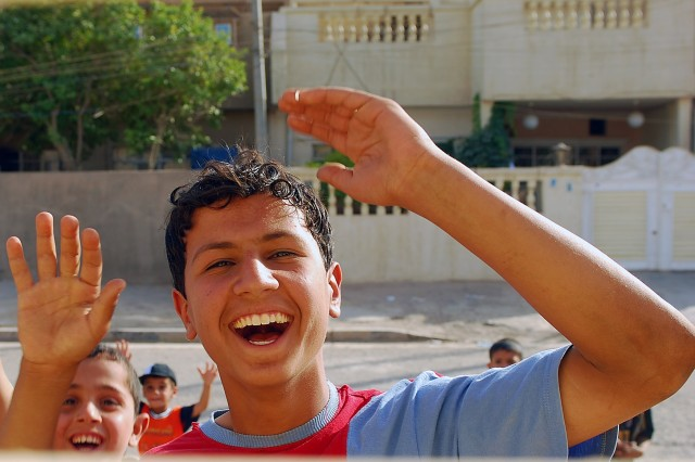 A group of Iraqi boys wave to the camera through an opening in the Al Murooa school for girls' gate during a visit by Soldiers from 3rd Platoon, Company A, 1st Combined Arms Battalion, 68th Armored Regiment, 3rd Brigade Combat Team, 4th Infantry Division, Multi-National-Division - Baghdad, May 12.