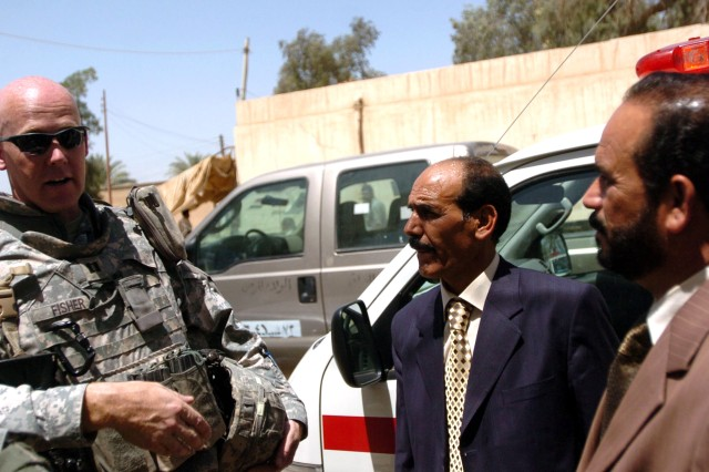 Captain Mike Fisher, commander of Battery B, 3-320th Field Artillery, speaks with Yaseen Mustafa, Lutifiyah Nahia Council chairman, and Abu Ammar, Mahmudiyah Qada Council chairman, in front of an ambulance delivered to the Lutifiyah Medical Clinic April 26.