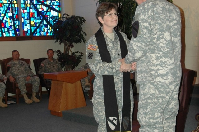 Springfield, Mo. native Chaplain (Lt. Col.) Barbara Sherer, the incoming 1st Cavalry Division chaplain, receives the 1st Cav. Div. stole from the division's commanding general Maj. Gen. Daniel P. Bolger, during a changing of the stole ceremony at the division's memorial chapel May 20. In receiving this sacred symbol she acknowledges and accepts her role as spiritual leader for the heavily-armored unit.