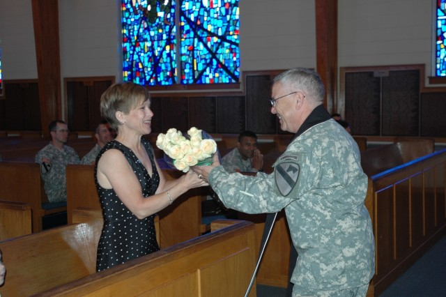 Chaplain (Lt. Col.) Steve Walsh, the 1st Cavalry Division's outgoing chaplain, hands his wife Lisa of Henrietta, Okla., a bouquet of yellow roses during a changing of the stole ceremony at the division's memorial chapel May 20.