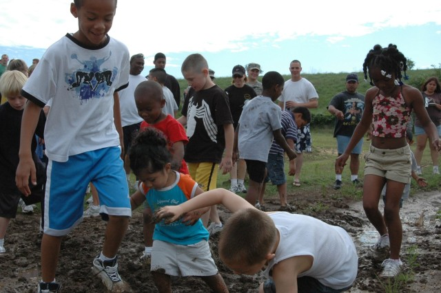 Children whose fathers serve in the 2nd Battalion, 5th Cavalry Regiment, play in the mud during the 2nd Bn., 5th Cav. Regt.'s 2nd Annual Mud Run May 17 at Fort Hood, Texas.