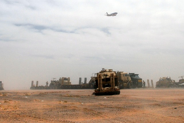 Soldiers of 96th Trans download their tank cargo May 12 at Fort Bliss, TX, as strong winds blow clouds of sand around the vehicles, within sight of the Mexican border.