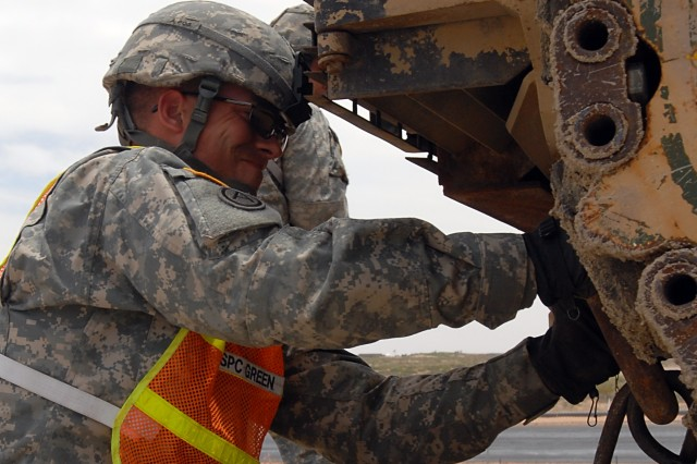 Spc. Keith Green, heavy wheeled vehicle operator 96th Trans, secures an M1A2 Abrams to a HET trailer here May 9.