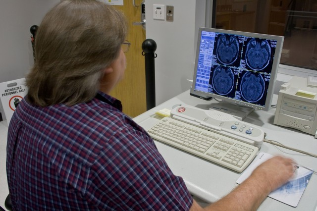 Ronnie Hunter, a chief technician and Vietnam veteran, scans the brain of a 1st Cavalry Soldier at the University of Texas. The scans will be used in a project to help identify how Post Traumatic Stress Disorder affects the brain.