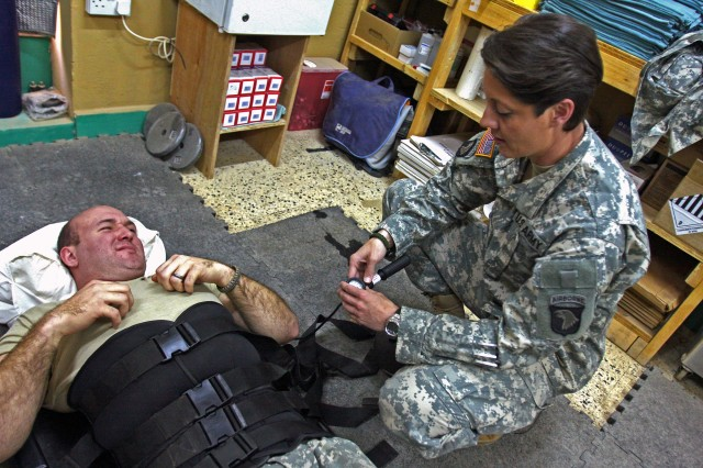 Staff Sgt. Gaither, physical therapist NCOIC, 1st Brigade Combat Team, 101st Airborne Division (AA), checks on a Soldier with back pain at the Combat Support Hospital here at Contingency Operating Base Speicher, Iraq.