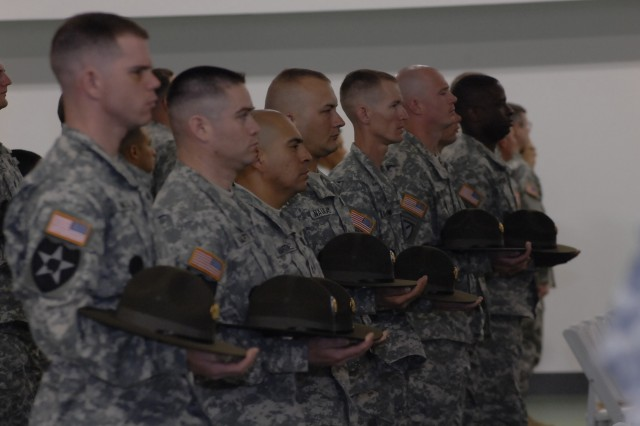 Students of Fort Leonard Wood's last drill sergeant class stand at attention during their graduation ceremony, Friday. The school closed after 44 years on post.