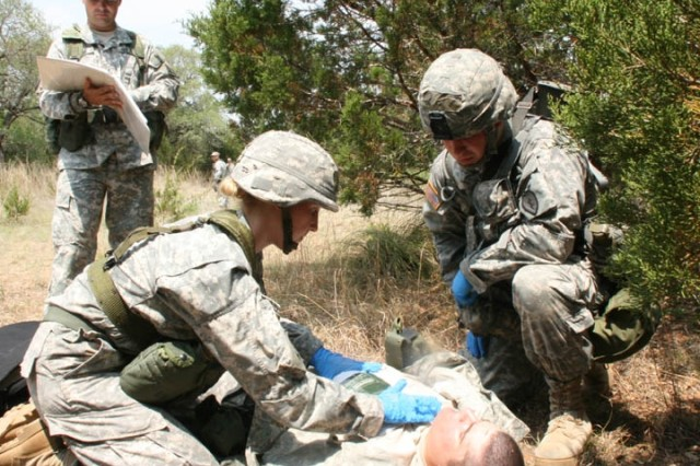 Second Lt. Samantha Rieger, 72D environmental officer (foreground left), administers first aid to a Soldier suffering from a chest wound and prepares the Soldier to be transported to a recovery vehicle. An evaluator ensures that Soldiers administer first aid as required by the regulation.