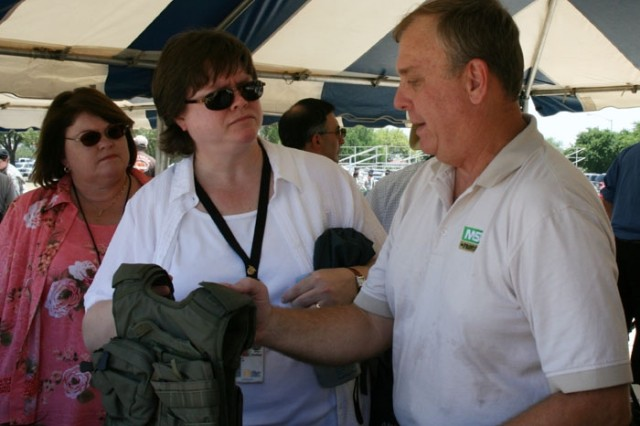 (From left) Josie Poirier and Laura Grindle listen as Keith Wells, of Mine Safety Appliances, explains the benefits of different flak vests worn by Special Forces and other Soldiers at Safety Day May 20.