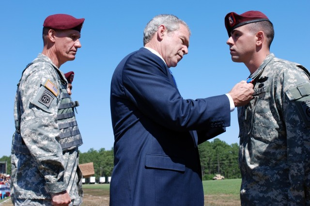 Sgt. Christopher Corriveau, Headquarters and Headquarters Company, 2nd Battalion, 505th Parachute Infantry Regiment, 3rd Brigade Combat Team, 82nd Airborne Division, is awarded the Distinguished Service Cross from President George W. Bush along with the commander of the 82nd Abn. Div. Maj. Gen. David Rodriguez May 22 during the Division's Review at Fort Bragg, N.C. Corriveau, a native of Lewiston, Maine,  is credited with repelling an overwhelming and heavily-armed force Aug. 26, 2007. His four man sniper team courageously fought off an enemy force in close combat for control of a rooftop during Operation Iraqi Freedom killing or wounding at least 10 insurgents.
