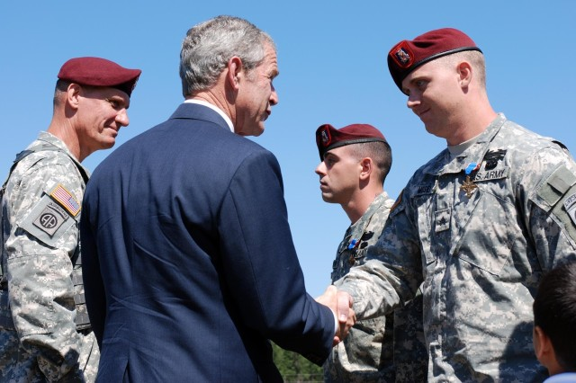 Sgt. Eric Moser (right), Charlie Company, 2nd Battalion, 505th Parachute Infantry Regiment, 3rd Brigade Combat Team, 82nd Airborne Division, is awarded the Distinguished Service Cross by President George W. Bush along with the commander of the 82nd Abn. Div. Maj. Gen. David Rodriguez May 22 during the Division's Review at Fort Bragg, N.C. Moser, a native of Houston, is credited with repelling an overwhelming and heavily-armed force Aug. 26, 2007. His four man sniper team courageously fought off an enemy force in close combat for control of a rooftop during Operation Iraqi Freedom killing or wounding at least 10 insurgents.
