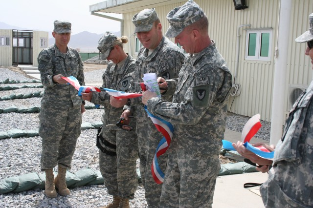 Col. Dennis M. Thompson (right), commander, 401st Army Field Support Brigade, and members of the brigade's forward staff, cut the ribbon opening the brigade's new headquarters at Bagram AirA-a,!A eld, Afghanistan.