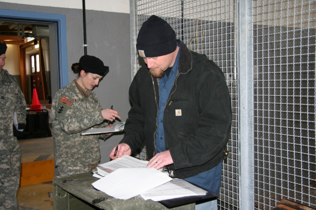 Capt. Penny Bloedel, commander of the 54th Engineer Battalion Field Support Company, double checks inventory numbers with Honeywell contractor Mike Hansen as she and her unit prepare to put their equipment into the LBE program prior to deployment.