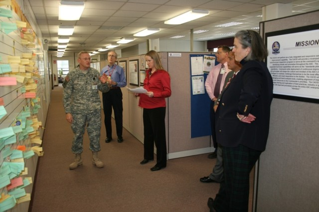 Maj. Gen. Robert M. Radin, commanding general of Army Sustainment Command, uses the E-Board to illustrate his point that continuous improvement is the engine that drives the Army Sustainment Command to Kathryn A. Condon, executive deputy to the commanding general, Army Materiel Command (far right).