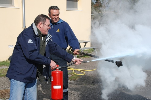 Fire inspector Massimo Ferrari (right) holds a torch for Alessandro Galeazzi(left), an Italian employee at 3/405th Army Field Support Battalion, to extinguish as part of the Fire Warden safety class.
