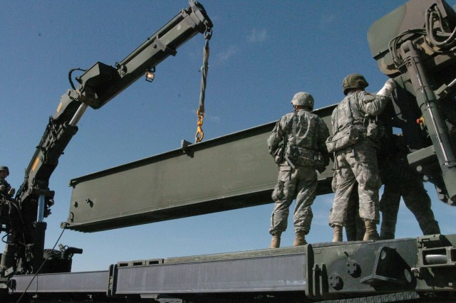 Soldiers with the 652nd Engineer Company unload a base component for a dry support bridge during training during Operation Sand Castle. The 652nd, an Army Reserve unit from Ellsworth, Wis., are using this training to simulate war time scenarios to ensure they are equipped and ready to accomplish their mission.