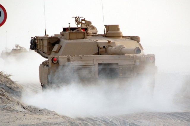 Their 120mm main guns facing to the rear, new M1 Abrams tanks kick up clouds of dust as they head for a 2nd Battalion, 401st Army Field Support Brigade Theater Sustainment Stock holding area at Camp Arifjan, Kuwait, Monday, May 19, 2008.