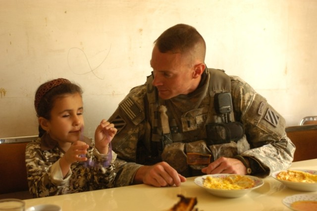 Noor, a young girl receiving eye surgery in the U.S., entertains 1st Lt. Michael Kendrick while he eats breakfast at her family's house in al-Buaytha, Iraq, May 25. Noor suffers from sclerocornea, a condition which has left her blind since birth. With help from Kendrick and other Soldiers of 1-30th Inf. Regt., she is traveling to the U.S. for surgery that may restore her vision.