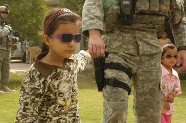 Noor, a young girl receiving eye surgery in the U.S., leads 1st Lt. Michael Kendrick on a walk through her yard in al-Buaytha May 25. Noor is wearing the sunglasses Kendrick's wife sent her as a gift.