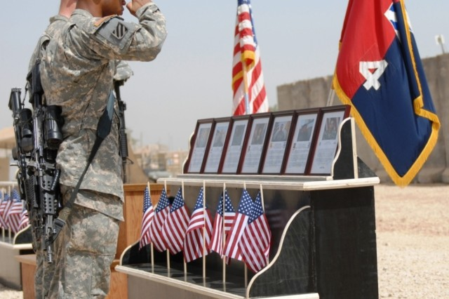 Private First Class Michael McDaniel and Spc. Raymond Goss, both with Co. A, 3-7th Inf. Regt., pay their respects to their fallen comrade, Spc. Kyle Norris, during a Memorial Day service May 26 at FOB Kalsu.