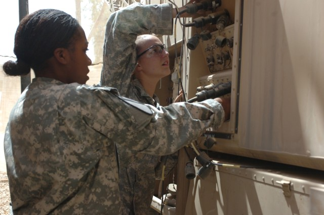 Telecommunications operator and maintainer Pfc. Ashley Bumpas, (left) and signal systems support specialist, Pvt. Sandy Ackerman, both in the communications and automation section, or S6 shop, of the 4th Brigade Combat Team, 1st Cavalry Division, check the fiber optic cables that connect all of the signal tactical vehicles together, at Forward Operating Base Marez, Iraq.