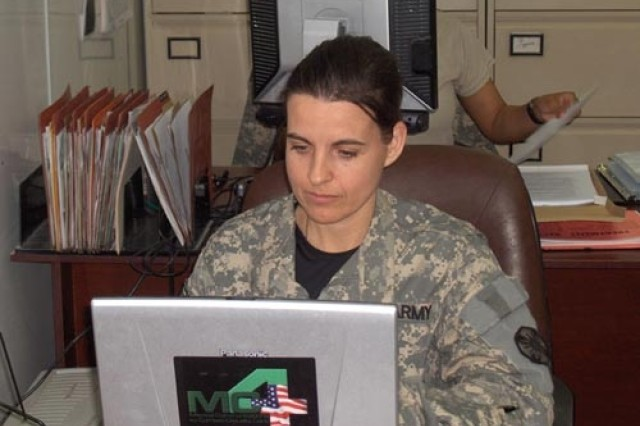 Task Force 21's MAJ Rhonda Clark, Patient Administration Division chief, enters patient data into the MC4 system.