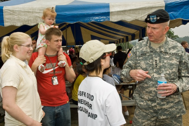 YONGSAN GARRISON, Republic of Korea -- Han Na-jeong, 17, from Daegu's Dongmoon High School, relates her English Camp experience to USFK Commander Gen. B.B. Bell. At left is her host family, Spc. Johnny Carter, his wife, Elizabeth, and their daughter, Abby.