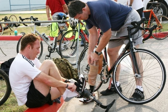 FORT SAM HOUSTON, Texas -- Kirk Simendinger, prosthetist from the Center for the Intrepid, assists Spc. Mark Roseberry with his prosthesis so he can start the 10-mile bike ride.