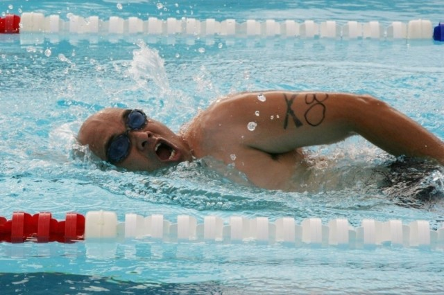 """FORT SAM HOUSTON, Texas -- Master Sgt. Dan Robles completes a 500-meter swim at the post's outdoor pool. Robles was one of several participants in a triathlon for wounded warriors May 23 sponsored by the Center for the Intrepid here. """"I had a great time,"""" Robles said. """"I swim a lot so that part was fun."""" The triathlon comprised a 2-mile run, 500-meter swim and 10-mile bike ride.  The CFI is a state-of-the-art physical rehabilitation center located next to Brooke Army Medical Center."""""""