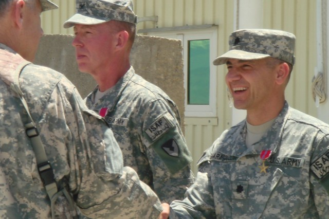 General Benjamin S. Griffin, commanding general, U.S. Army Materiel Command, congratulates Lt. Col. Iraj Gharagouzloo, commander, 3rd Battalion, 401st Army Field Support Brigade after presenting him with a Bronze Star for meritorious service. Col. Dennis M. Thompson (left center), outgoing 401st AFSB commander was decorated with the Legion of Merit. Not shown: Lt. Col. Robert B. Brown III was also awarded a Bronze Star at this May 24, 2008, ceremony at Bagram Airfield, Afghanistan.
