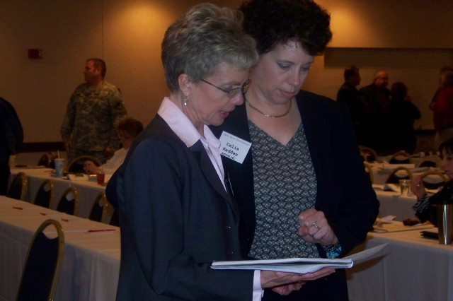 Kristine Preston, chief, Installation Advocacy and Workload Integration Office for the Joint Munitions Command, left, confers with Celia Hadden, assistant deputy, JMC's Munitions and Logistics Readiness Center, at the Spring Warm Base Conference held March 31-April 1.