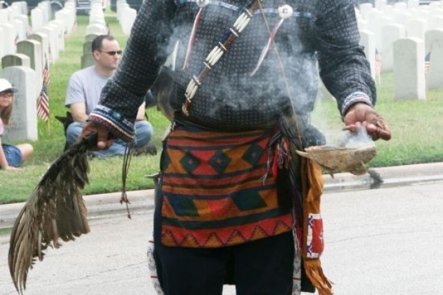 """Miguel Sanchez, from the Native American community, burns sage to cleanse, or """"smudge,"""" the area in honor of fallen servicemembers during the Memorial Day ceremony at the Fort Sam Houston National Cemetery."""