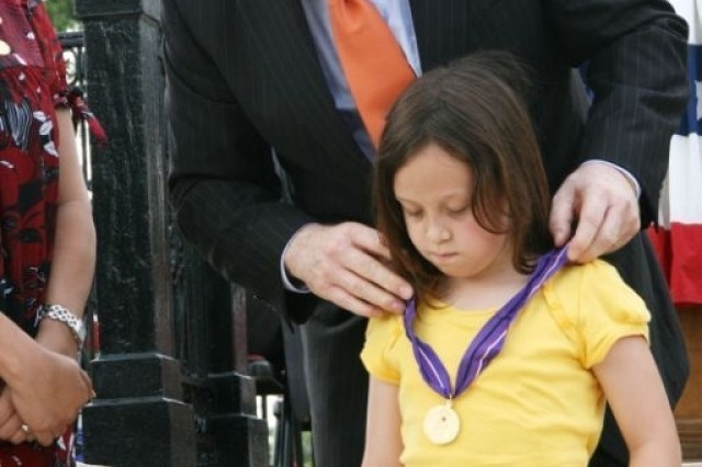 U.S. Senator John Cornyn presents 7-year-old Shannon Frantz with a Gold Medal of Remembrance. Shannon is the daughter of Pvt. Robert Frantz, who was wounded in Baghdad, Iraq, when a resident threw a grenade over the wall. He died June 17, 2003.  The medal recognizes and honors children who recently lost a parent in service to the nation.