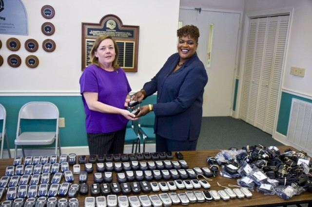 Anniston Army Depot Director of Information Management Alberta Freeman (right) is on hand May 19 at the United Way in Anniston, Ala., to officially hand over more than 100 cellular phones to Susan Shipman (left), executive director of 2nd Chance, a non-profit organization that helps victims of domestic violence.