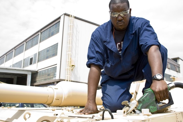 Dennis McGee, a heavy mobile equipment mechanic, pumps fuel in a M1 tank at Anniston Army Depot, Ala.