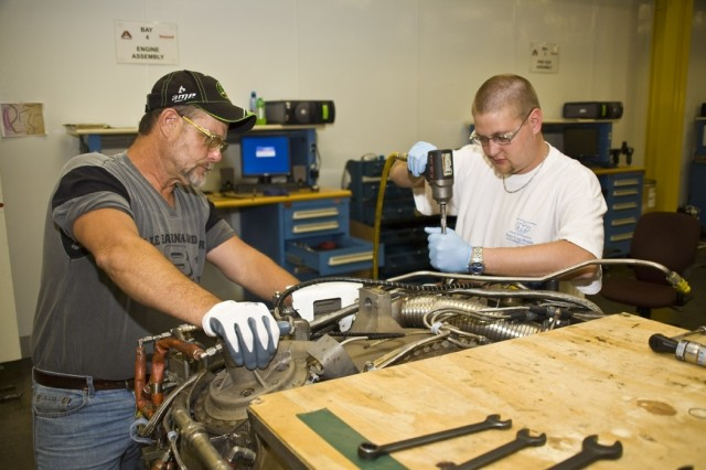 Alex Rogers (left) and Derrick Clark, both mechanics, build an AGT 1500 engine to be used in an Egyptian M1 tank. In public-private partnership, Anniston Army Depot, Ala., and contractor Honeywell delivered their 100th new engine on May 21.