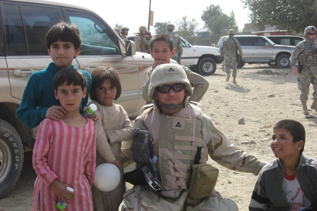 Randy Bright, a depot engineer, poses with children from a refugee camp in Kabul, Afghanistan during a Volunteer Community Relations project in October 2007.