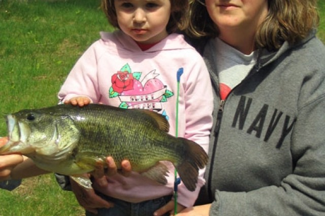 Kimberly Gilmore, 3, poses with the overall largest fish caught at the 12 Annual Fort Drum Fishing Derby, an 18-inch largemouth bass, as her mother, Tammy Narrow, looks on.