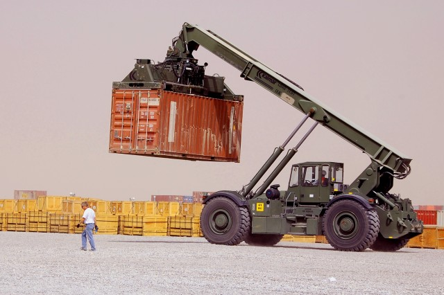 Floyd Woods, a 401st Army Field Support Brigade supply technician with Lockheed Martin Information Technology Corporation, is dwarfed by a passing rough terrain cargo handler carrying a container at Camp Arifjan, Kuwait, Thursday, May 29, 2008.