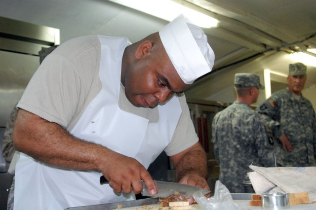 Staff Sgt. Michael Purnell, a member of Team Lifeliner, slices into beef as he prepares a meal for the Iron Chef  competition at Bagram Airfield on May 28.