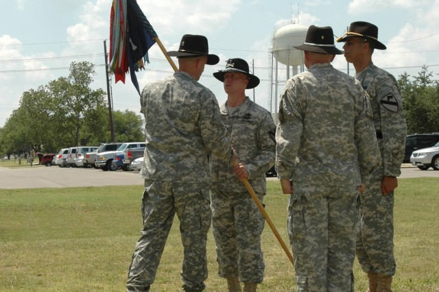 The Division Special Troops Battalion commander Lt. Col. Matthew G. Karres passes the band's colors to the band's incoming commander Chief Warrant Officer 4 Aaron Graff during a change of command ceremony held in front of the division's music hall May 29.