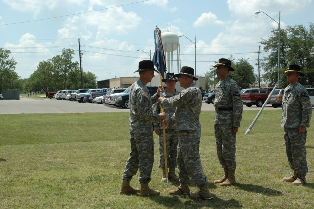 The 1st Cavalry Division band's outgoing commander Chief Warrant Officer 4 Glen Nardin passes the guidion to the Division Special Troops Battalion commander Lt. Col. Matthew G. Karres in a change of command ceremony held in front of the division's music hall May 29.