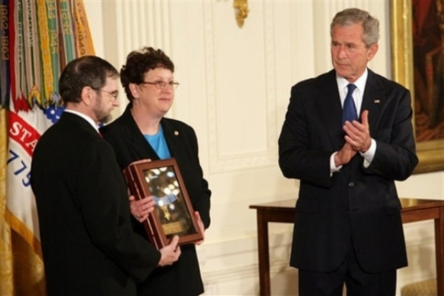 President George W. Bush leads the applause to honor Pfc. Ross A. McGinnis after presenting the Congressional Medal of Honor posthumously to his parents, Tom and Romayne McGinnis, of Knox, Pa., June 2, at the White House.