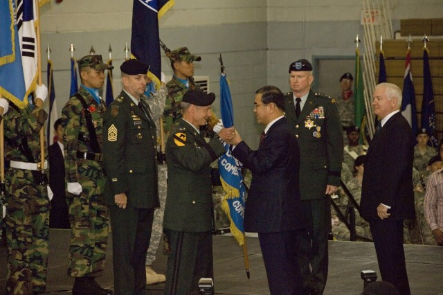 YONGSAN GARRISON, Republic or Korea - Republic of Korea Defense Minister Lee Sang-hee passes the ROK/U.S. Combined Forces Command flag to Gen. Walter L. Sharp, who today assumed command of United Nations Command, Combined Forces Command and U.S. Forces Korea. Sharp succeeds Gen. B.B. Bell (behind Minister Lee) who is retiring after 39 years in the Army. At right is U.S. Secretary of Defense Robert Gates.