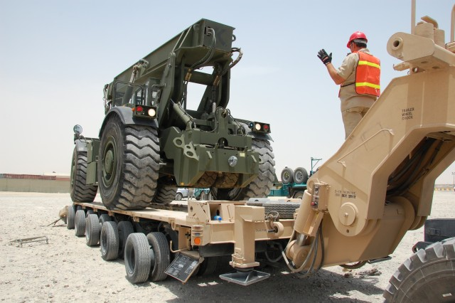 A worker guides a new, 59-ton, RT 240 \'Kalmar' Rough Terrain Container Handler, bound for use in Operation Iraqi Freedom, into position on an M1000 Heavy Equipment Transport Semitrailer, Monday, June 3, 2008 at Camp Arifjan, Kuwait.