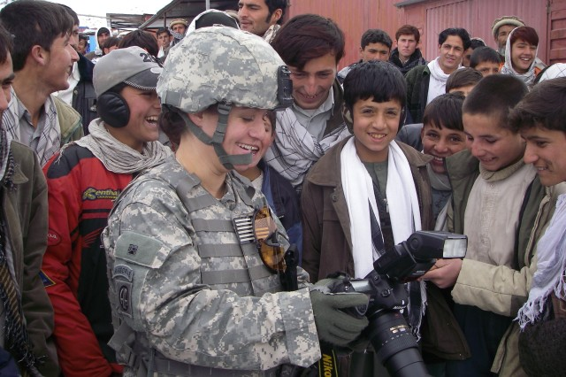 Staff Sgt. Tyffani Davis, 55th Signal Company (Combat Camera) performs ad hoc outreach, showing her digital photos to some Afghan youth.