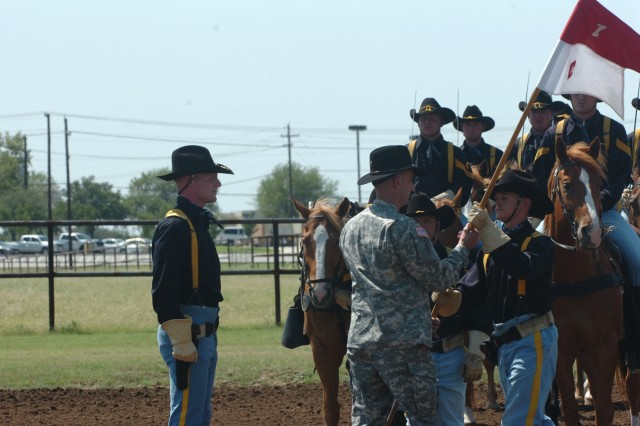 The outgoing commander of the 1st Cavalry Division's Horse Cavalry Detachment Capt. Ted Zagraniski (right) relinquishes command to Capt. Jay Bunte (far left) during a horse-mounted change of command ceremony May 30 at Fort Hood, Texas.