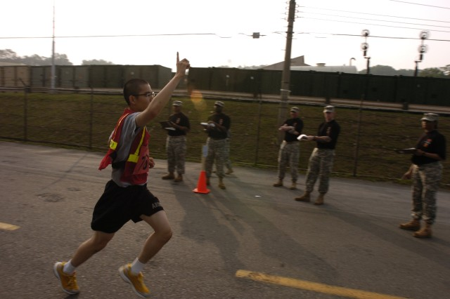 Cpl. Lee, Dong Kyoon, an administration clerk for the 35th Air Defense Artillery Brigade, 144th Company, steps over the finish line first followed by Staff Sgt. Joshua Bynum, a patriot missile operator for the 35th Air Defense Artillery Brigade, 144th Company, during the 2008 8th Army Best Warrior Competition Army Physical Fitness Test at Camp Carroll, Korea June 3. Lee's run time was 11 minutes and 40 seconds and Bynum's time was 1152. Lee is competing for Korean Augmentee to the United States Army of the Year.
