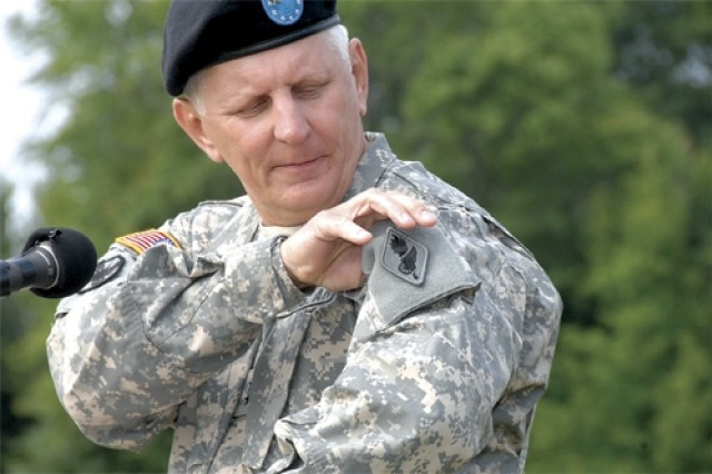 Maj. Gen. James E. Chambers removes his old unit shoulder patch at the podium during the CASCOM change of command ceremony held June 3 at the 23rd Quartermaster Brigade sports field, Fort Lee, Va.